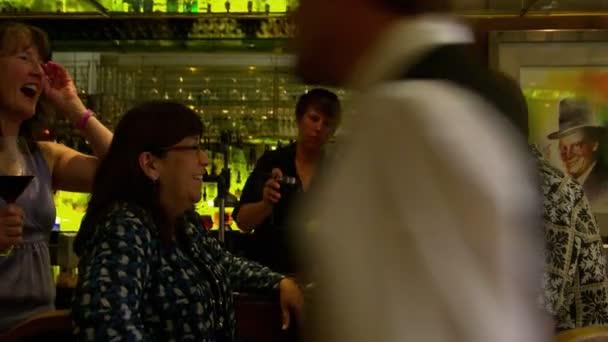 Panning shot of people at a bar