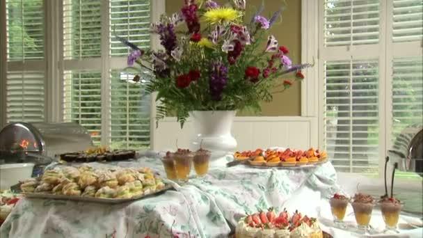 Záběr ze za stůl plný dezertů.
