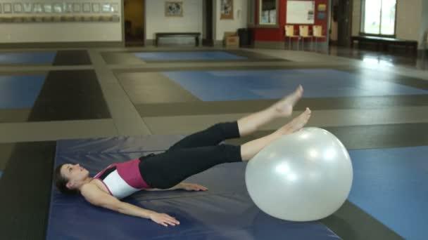 Dívka noha výtahy s fitness míče