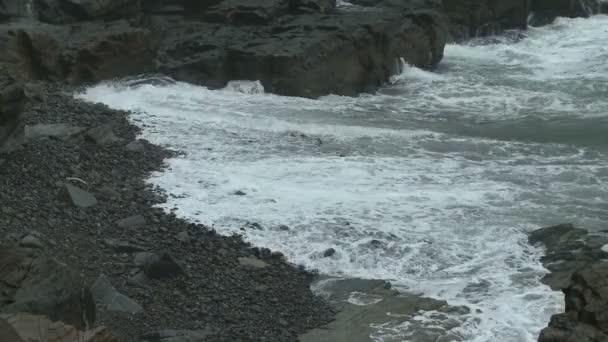 Wellen in Schaum auf einem felsigen Strand in Maine.