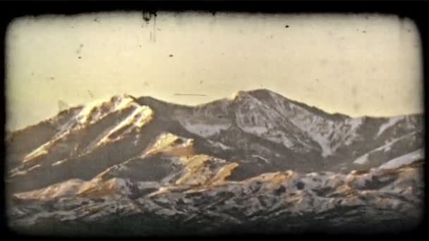 Snow capped mountains. Vintage stylized video clip.