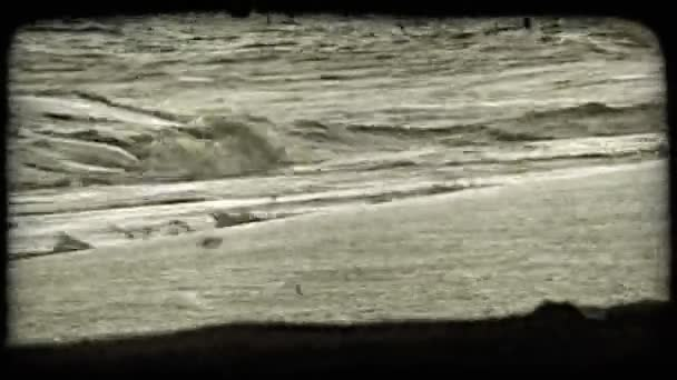 Waves break against sandy beach. Vintage stylized video clip.