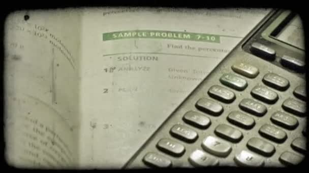 Close-up pan of math textbook and graphing calculator.