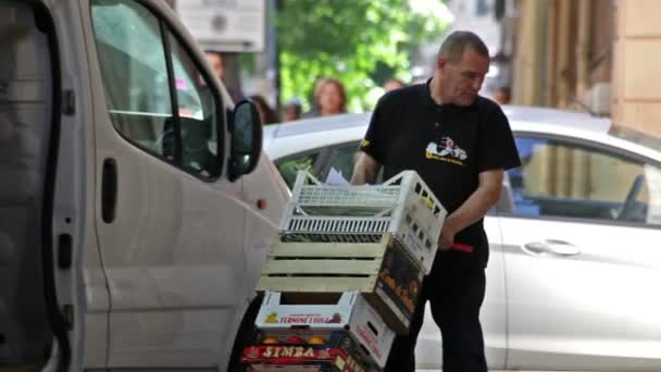 A produce-delivery man brings his wares into a building in Rome, Italy.