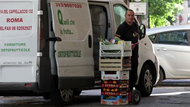A delivery man stands next to his delivery van and a stack of fruit in Rome, Italy.
