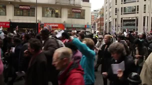 Průvod lidí chodí na ulici v Londýně