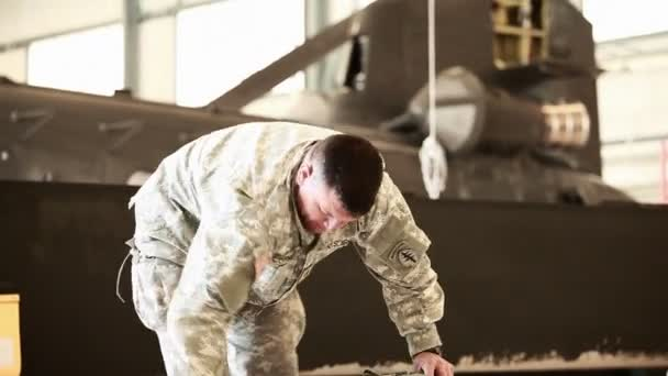 Soldier preparing his gear in a hangar