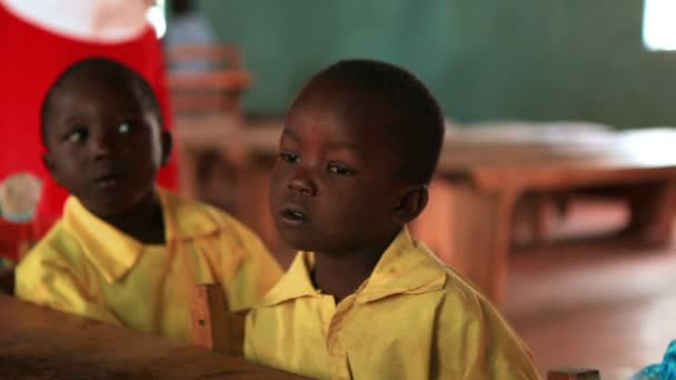 Cute African children sing at a small table in a Kenya, Africa school building