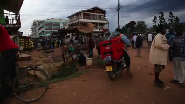 Tracking footage of Kenyan town road filled with people, vehicles