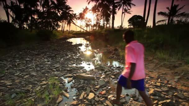 Chlapec šel podél skalní potok v Africe při západu slunce