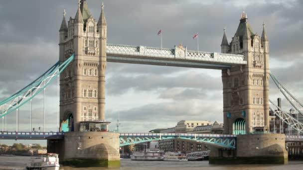 Tower Bridge bascules raising, boats pass under in London