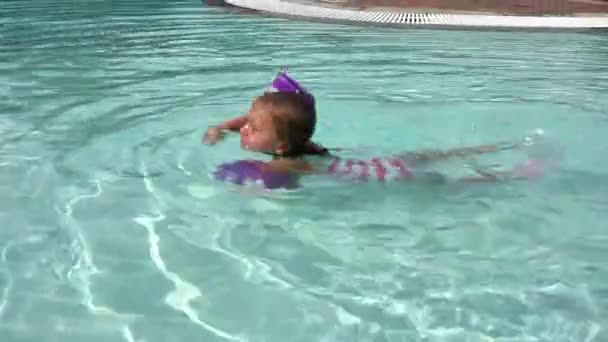 little girl paddling in a pool