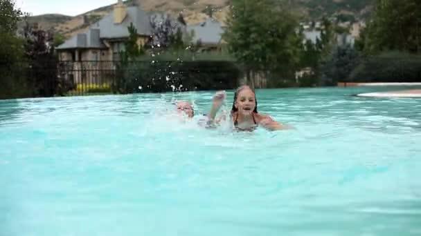 little girls splashing in a pool