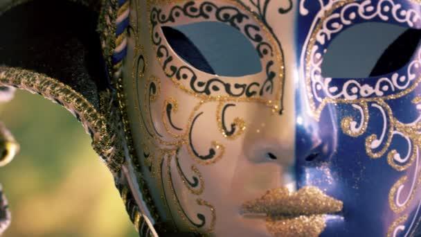 Nahaufnahme einer kunstvollen Karnevalsmaske, die im Wind weht.