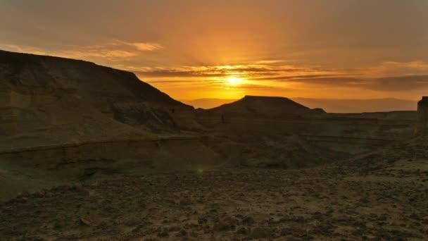 Clouds moving across desert sky during orange sunset