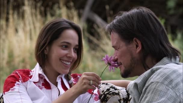 žena přijímá fialový květ od muže
