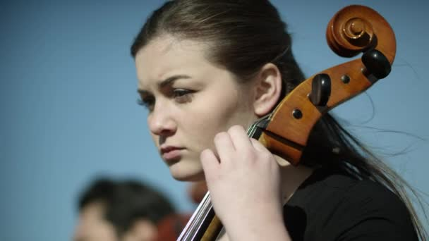 nő játszik a cselló egy szabadtéri zenekar