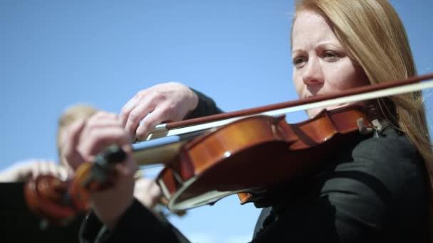 Frau spielt die Violine in einem Outdoor-Orchester