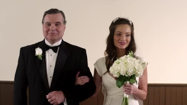 padre e sposa che cammina lungo la navata