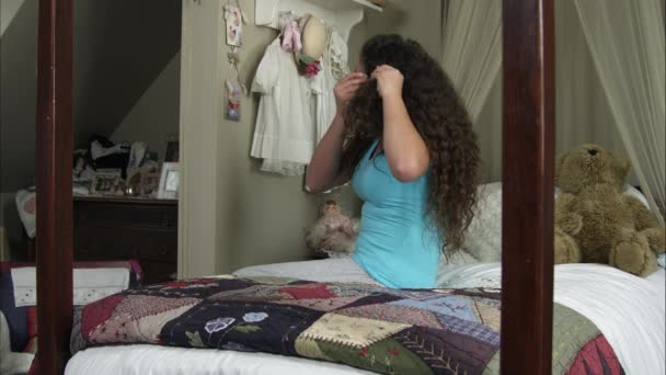 girl putting a barrette into her hair.