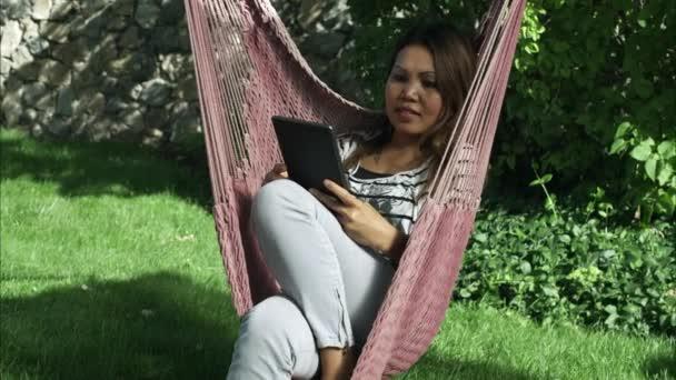 Asijská žena čte něco v její tablet při posezení na houpací síť