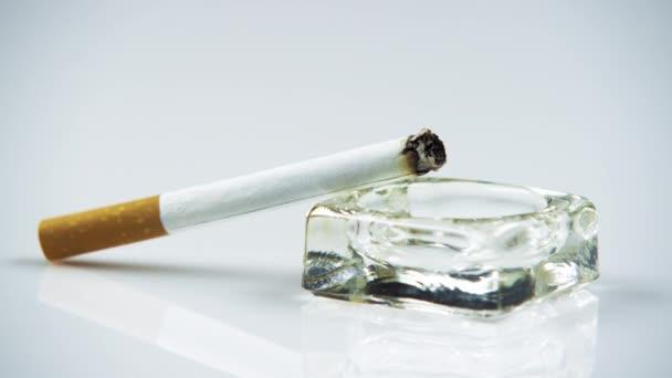 zapálil cigaretu v popelníku.