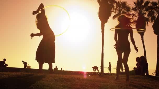 zwei Frauen spielen mit Hula-Hoop-Reifen