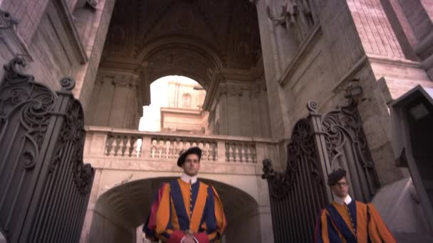 The camera tilits up from two Swiss Guards