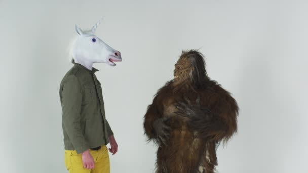 hairy beast and man with a unicorn head embracing