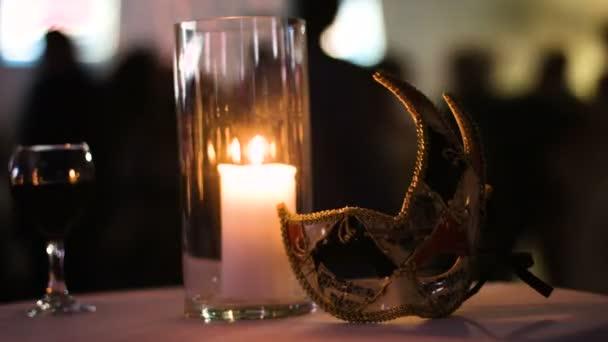 Obrázek pálení svíčky ve skleněných pohár, sklenici červeného vína a karnevalovou masku leží na stole v klubu, lidé tančí na pozadí