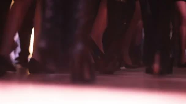 Houf lidí, kteří tančí na taneční parket, close-up záběrů lidí aktivně pohybuje nohama na hudbu. Tančící nohy s disco světla
