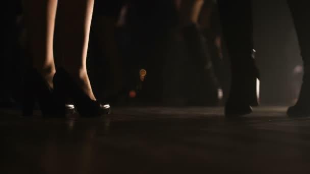 Nahaufnahme Bild von zwei weiblichen Beinpaare auf Fersen auf einer Tanzfläche tanzen.