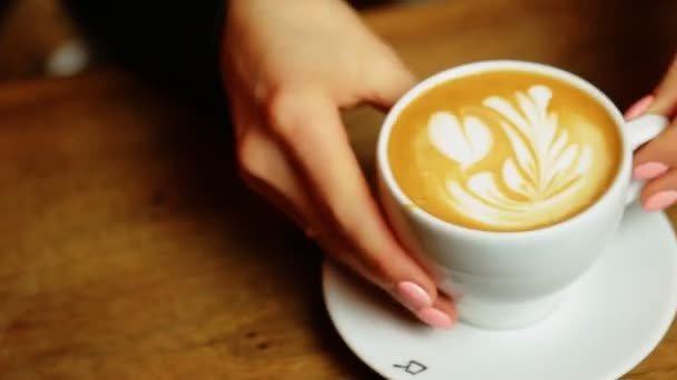 Womens hands puts a white cup of coffee on the table and then puts a spoon.