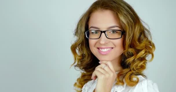 Detail portrétu atraktivní mladá žena v brýle pózy a úsměvy v ateliéru.