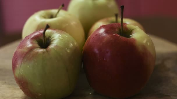 Close-up footage of fresh and wet green and red mixed apples lie on a wooden board  which is spinning around.