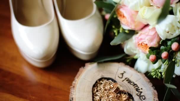 Chiuda in su della decorazione di cerimonia nuziale fatta di belle scarpe bianche, basamento di legno per fedi nuziali e mazzo di fiori