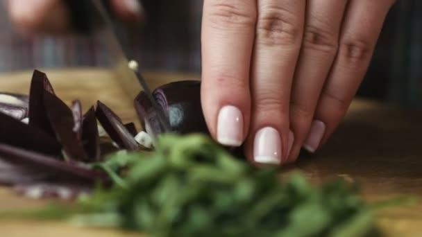 Mladá hospodyňka slicingred cibuli na kroužky na tablewith nůž na prkně.