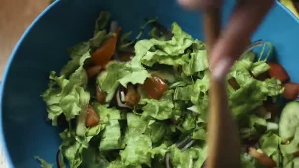 Ženské ruce míchání zeleninový salát připravit chutné zelené okurky, salátových listů, červená cibule a rajčat