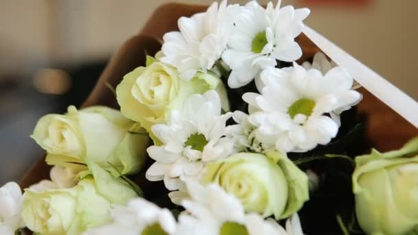 A bouquet of white roses and chamomiles.
