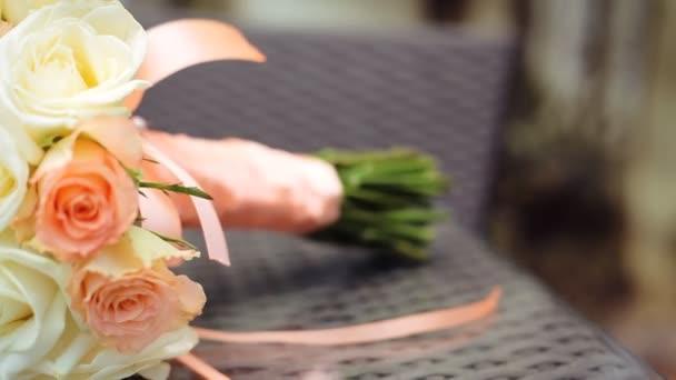 Svatební kytice z oranžových a bílých růží na hnědý dřevěný stůl
