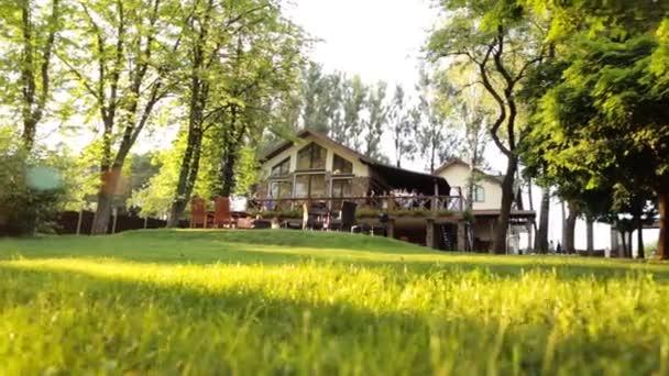 Lidé se těší letní den na terase café v stínu zelených stromů v zahradě poblíž dřevěné budovy