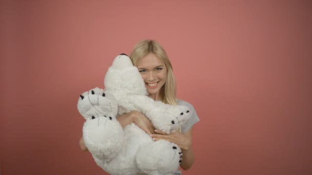Beautiful blonde woman posing in the studio hugging a teddy bear
