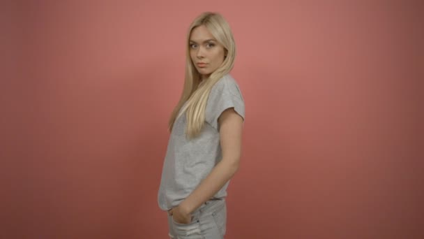 Fashion. Young blonde fashionable woman in gray outfit. Female model posing isolated on pink background