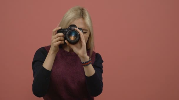 Attractive blonde woman taking photos with camera and laughing against pink background
