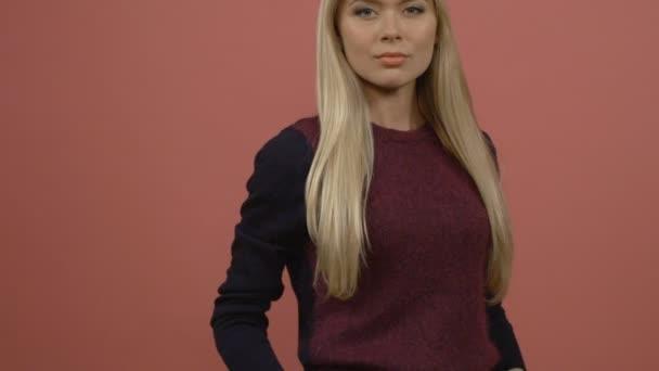 Közelről Leányi súlyos szőke, barna inget, rózsaszín falnak állandó, és bámulta a kamera visel.