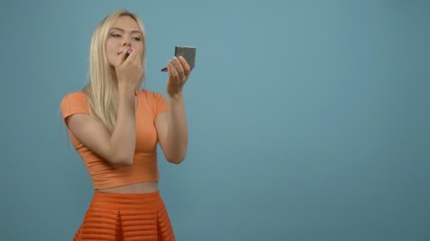 Rty make-up. Usmíval se blondýnka v oranžové nejvyšší vyrovnávací Pomáda s zrcadlo, modré pozadí