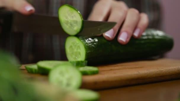 Egy nő uborkát szeletel. A női kezek zöld uborkás gyűrűket vágnak. Nagy kés. A konyhában. Fa deszka. Egy házra büszke nő. Friss uborka. Friss zöldség. éles kés.