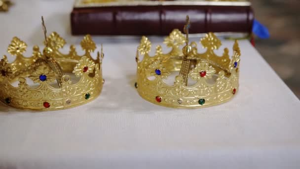 Two golden crowns and bible on white table prepared for wedding ceremony