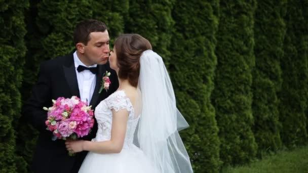 Happy nádherná nevěsta svatební kytice růžová a stylový ženich objímala s jemným, líbání na pozadí slunné stromy lesa