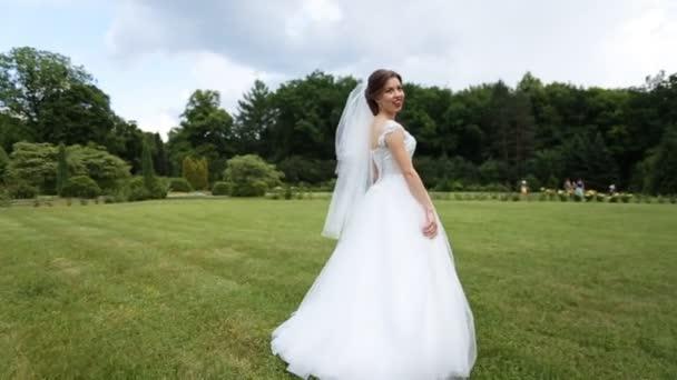 f9aeaef742 Hermosa novia posando en vestido blanco y velo al aire libre